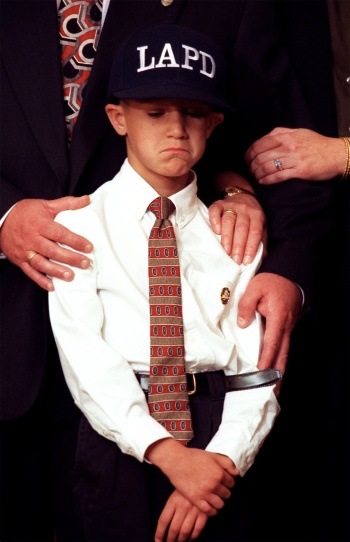 ME.Son.1.1203.RM--Dylon Brown, age 7, shows some grief at a press conference held at LAPD's Parker Certer. He is supported with the hands of his grandparents. They are Dennis and April Brown. THU folder. Photo shot in Los Angeles on 12.3.98. Rick Meyer/LAT Photo/Art by:Rick Meyer